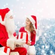Smiling little girl with santa claus and gifts — Stock Photo #58461639