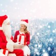 Smiling little girl with santa claus and gifts — Stock Photo #58461675