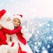 Smiling little girl with santa claus and gifts — Stock Photo #58461841