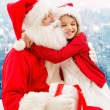 Smiling little girl with santa claus and gifts — Stock Photo #58462001