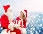 Smiling little girl with santa claus and gifts — ストック写真