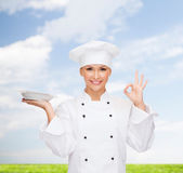 Smiling female chef with plate showing ok sign — Stock Photo