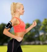 Sporty woman running with smartphone and earphones — Stock Photo