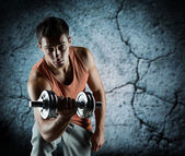 Young man with dumbbell flexing biceps — Stock Photo