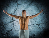 Young male bodybuilder with raised hands — Stock Photo