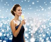Smiling woman holding glass of sparkling wine — Stock Photo