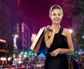 Smiling woman in evening dress with shopping bags — Stock Photo