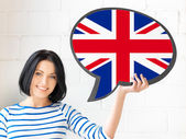 Smiling woman with text bubble of british flag — Photo