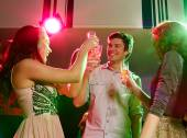Smiling friends with glasses of champagne in club — Stock Photo