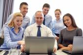 Smiling business people with laptop in office — Stock Photo