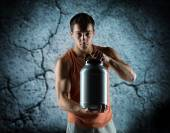 Young male bodybuilder holding jar with protein — Stock Photo