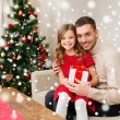 Smiling father and daughter holding gift box — Stock Photo #58617841