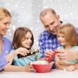Happy family with two kids making salad at home — Stock Photo #58618403