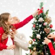 Smiling family decorating christmas tree at home — Stock Photo #58619127