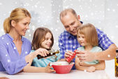Happy family with two kids making salad at home — Stock Photo