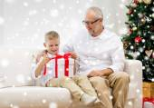 Smiling grandfather and grandson with gift box — Stock Photo