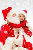 Smiling girl hugging santa claus with gift at home — Stok fotoğraf