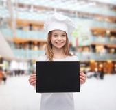 Little cook or baker with blank black paper — Stock Photo