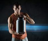 蛋白質が付いている瓶を保持している若い男性のボディービルダー — ストック写真