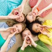 Smiling people lying down on floor and screaming — Stock Photo
