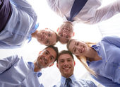Smiling group of businesspeople standing in circle — Stock Photo