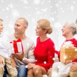 Smiling family with gifts talking at home — Stock Photo #58825493