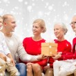 Smiling family with gift at home — Stock Photo #58825503