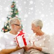 Happy senior couple with gift box at home — Stock Photo #58826139