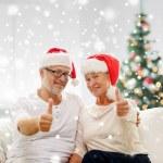 Happy senior couple in santa helper hats — Stock Photo #58826273