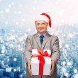 Smiling man in suit and santa helper hat with gift — Stock Photo #58828147