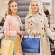 Happy young women with shopping bags in mall — Stock Photo #58829669