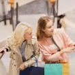 Happy young women with shopping bags in mall — Stock Photo #58829677