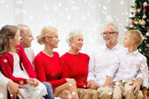 Smiling family sitting and talking at home — Stock Photo