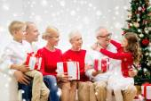Smiling family with gifts hugging at home — Stock Photo