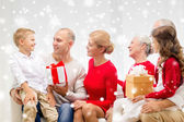 Smiling family with gifts talking at home — Stock Photo