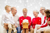 Smiling family with gift at home — Stock Photo