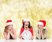 Mujeres sonrientes en sombrero de ayudante de santa con reloj — Foto de Stock
