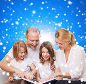 Happy family with book at home — Stock Photo