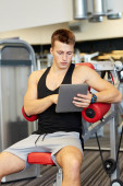 Young man with tablet pc computer in gym — Stock Photo