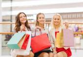Happy young women with shopping bags in mall — Stock Photo