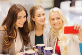 Smiling young women with cups and smartphone — Stock Photo