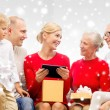 Smiling family with tablet pc and gift box at home — Stock Photo #58870569