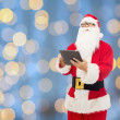 Man in costume of santa claus with tablet pc — Stock Photo #58870645
