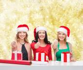 Smiling women in santa helper hats packing gifts — Stock Photo