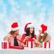 Smiling women in santa helper hats packing gifts — Stock Photo #58899011