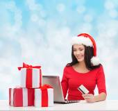 Smiling woman with gifts, laptop and credit card — Stock Photo