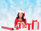 Smiling woman in santa helper hats packing gifts — Stock Photo