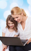 Smiling mother and little girl with laptop — Stock Photo