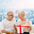 Happy senior couple with gift box at home — Stock Photo #58900903