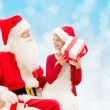 Smiling little girl with santa claus and gifts — Stock Photo #58903305